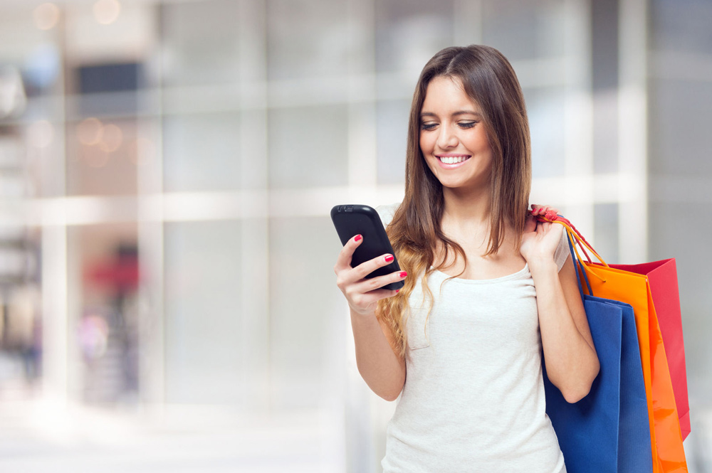 Young woman holding shopping bags looking at her phone
